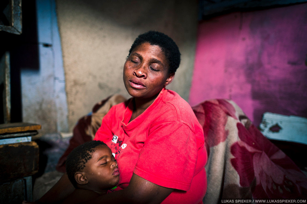 Betty Tyopolwana with one of her eight children at home in their shack in Imizano Yethu, an informal settlement in Hout Bay, South Africa. In Imizamo Yethu, 20'000 to 30'000 people live in a 18 hectare area with little or no infrastructure, two-thirds of them in informal dwellings and shacks. Many of the shacks do not have electricity. Only 19 percent of people have access to piped water in dwelling. Rain often moistens the shack interiors as the roofs are leaky.