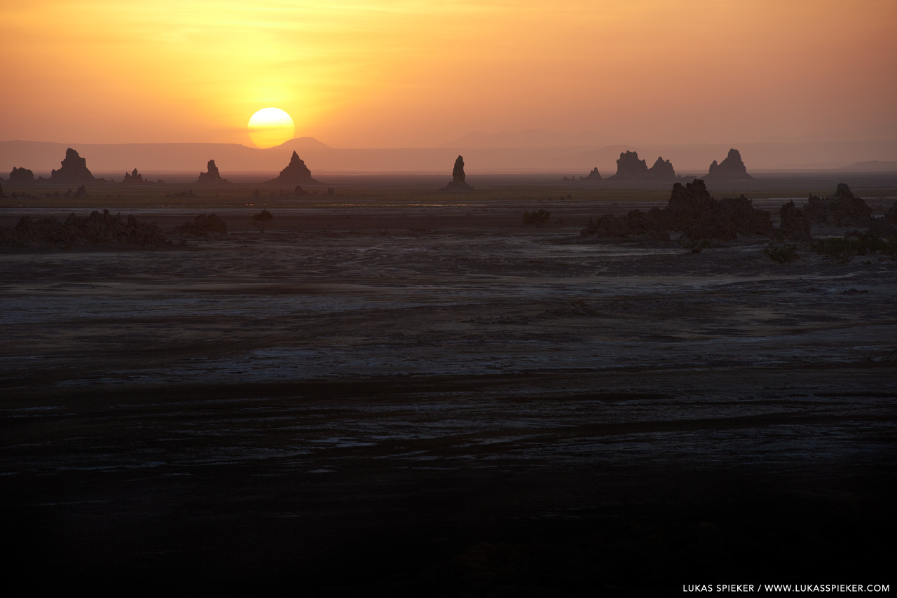 The sun sets behind limestone chimneys with steaming hot springs near Lac Abbe at the border between Djibouti and Ethiopia. Lac Abbe is a salt lake in the centre of the Afar Depression in the North of the East African Rift. The area is inhabited by Afar people herding camels, sheep, and goats.