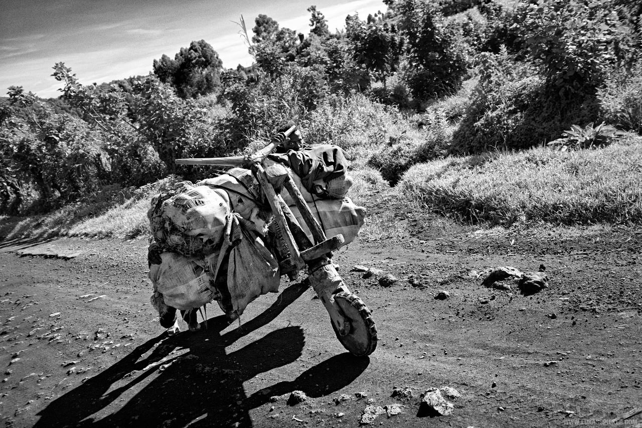 Men push a Chukudu, a wooden cargo bicycle, loaded with heavy sacks uphill on the road from Goma to the North in the Democratic Republic of the Congo.